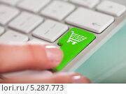 Палец нажимает на зеленую кнопку с пиктограммой покупательской корзины. Стоковое фото, фотограф Андрей Попов / Фотобанк Лори