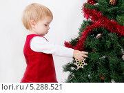 Купить «Маленькая девочка стоит около новогодней елки», фото № 5288521, снято 24 октября 2013 г. (c) Asja Sirova / Фотобанк Лори