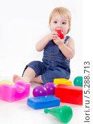 Купить «Маленькая девочка играет с пластиковыми кубиками на светлом фоне», фото № 5288713, снято 24 октября 2013 г. (c) Asja Sirova / Фотобанк Лори