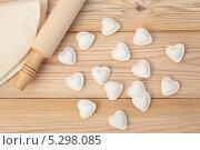 Пельмени в форме сердца, тесто и скалка на деревянном столе. Стоковое фото, фотограф Владимир Семенчук / Фотобанк Лори