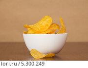Купить «Картофельные чипсы в белой миске на деревянном столе», фото № 5300249, снято 8 мая 2013 г. (c) Сергей Молодиков / Фотобанк Лори