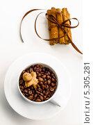 Кофейные зерна в белой чашке и корица, на белом фоне. Стоковое фото, фотограф Olena Gorbenko / Фотобанк Лори