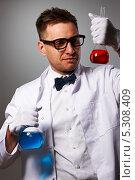 Мужчина в белом лабораторном халате держит колбы с цветными жидкостями. Стоковое фото, фотограф Николай Охитин / Фотобанк Лори