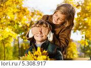 Светловолосая девочка закрывает ладонями глаза мальчику, сидящему на скамейке в осеннем парке. Стоковое фото, фотограф Сергей Новиков / Фотобанк Лори
