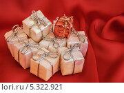Подарочки на красном, атласном фоне. Стоковое фото, фотограф Игорь Мицкевич / Фотобанк Лори