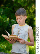 Купить «Мальчик-подросток читает книгу на прогулке», эксклюзивное фото № 5326305, снято 6 июня 2013 г. (c) Игорь Низов / Фотобанк Лори