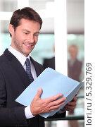 Купить «Менеджер читает документы в папке», фото № 5329769, снято 19 мая 2010 г. (c) Phovoir Images / Фотобанк Лори