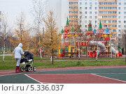 Купить «Женщина гуляет вдоль спортивной площадки рядом с детским игровым городком», эксклюзивное фото № 5336037, снято 6 ноября 2013 г. (c) Родион Власов / Фотобанк Лори