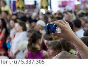 Купить «Съёмка смартфоном. Рука со смартфоном на фоне толпы людей.», фото № 5337305, снято 3 февраля 2012 г. (c) Владимир Заворохин / Фотобанк Лори