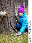Девочка манит белку угощением. Стоковое фото, фотограф Serg Zastavkin / Фотобанк Лори