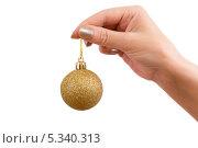 Золотой новогодний шарик в женской руке на белом фоне. Стоковое фото, фотограф Pavel Kozlovsky / Фотобанк Лори
