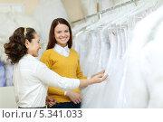 Купить «Консультант в свадебном салоне показывает невесте платья», фото № 5341033, снято 19 декабря 2012 г. (c) Яков Филимонов / Фотобанк Лори