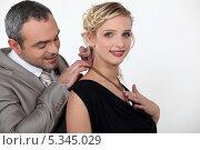 Купить «Мужчина надевает кулон на шею девушке», фото № 5345029, снято 6 декабря 2010 г. (c) Phovoir Images / Фотобанк Лори