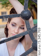 Купить «Портрет девушки у решётки ворот», фото № 5345769, снято 18 июля 2013 г. (c) Александра Орехова / Фотобанк Лори