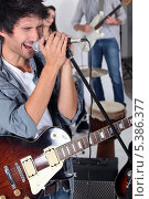 Поющий мужчина с гитарой. Стоковое фото, фотограф Phovoir Images / Фотобанк Лори
