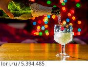 Шампанское льется в бокал на праздничном фоне с боке. Стоковое фото, фотограф Антон Куделин / Фотобанк Лори