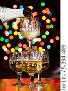 Игристое вино наливают в бокалы на праздничном фоне с эффектом боке. Стоковое фото, фотограф Антон Куделин / Фотобанк Лори