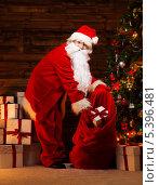 Купить «Санта Клаус складывает подарки в большой красный мешок», фото № 5396481, снято 4 октября 2013 г. (c) Andrejs Pidjass / Фотобанк Лори