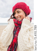 Cute smiling woman in warm clothing looking away at beach. Стоковое фото, агентство Wavebreak Media / Фотобанк Лори