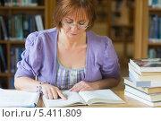 Купить «Mature female student studying at desk in the library», фото № 5411809, снято 28 августа 2013 г. (c) Wavebreak Media / Фотобанк Лори