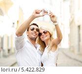 Купить «путешествующая пара фотографируется на камеру смартфона на улице», фото № 5422829, снято 14 июля 2013 г. (c) Syda Productions / Фотобанк Лори