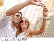 Купить «путешествующая пара фотографируется на улице», фото № 5423061, снято 14 июля 2013 г. (c) Syda Productions / Фотобанк Лори