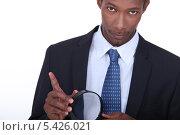 Купить «Темнокожий мужчина с увеличительным стеклом», фото № 5426021, снято 26 июля 2010 г. (c) Phovoir Images / Фотобанк Лори
