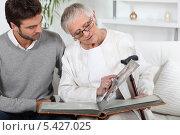 Купить «Пожилая женщина показывает молодому мужчине фотографии в фотоальбоме», фото № 5427025, снято 11 мая 2010 г. (c) Phovoir Images / Фотобанк Лори