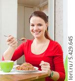 Женщина в красном ест гречку. Стоковое фото, фотограф Яков Филимонов / Фотобанк Лори
