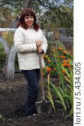 Купить «Женщина в светлой куртке стоит с лопатой», фото № 5434005, снято 20 сентября 2013 г. (c) EgleKa / Фотобанк Лори