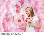 блондинка с букетом цветов читает открытку на розовом фоне. Стоковое фото, фотограф Syda Productions / Фотобанк Лори
