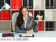 Купить «Молодая деловая женщина сидит на рабочем месте в офисе с моделью самолета. Туристическая фирма.», фото № 5506685, снято 12 октября 2013 г. (c) Мельников Дмитрий / Фотобанк Лори