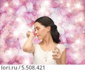 Купить «красивая брюнетка наслаждается ароматом своих духов», фото № 5508421, снято 2 марта 2013 г. (c) Syda Productions / Фотобанк Лори
