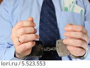 Купить «Бизнесмен держит перед собой руки в наручниках, в кармане рубашки лежат деньги», фото № 5523553, снято 21 января 2014 г. (c) Алексей Карпов / Фотобанк Лори