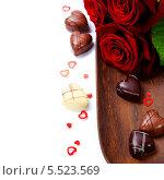 Купить «Розы и шоколадные конфеты на деревянной доске», фото № 5523569, снято 1 февраля 2013 г. (c) Наталия Кленова / Фотобанк Лори
