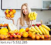 Купить «Позитивная девушка со свежими фруктами на кухне», фото № 5532285, снято 19 июня 2013 г. (c) Яков Филимонов / Фотобанк Лори