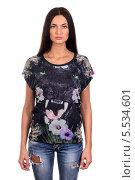 Купить «Молодая брюнетка в модной футболке и рваных джинсах, изолированно на белом фоне», фото № 5534601, снято 29 октября 2013 г. (c) Egorius / Фотобанк Лори