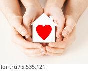 Купить «пара держит в ладонях бумажный домик с изображением сердца», фото № 5535121, снято 28 марта 2013 г. (c) Syda Productions / Фотобанк Лори