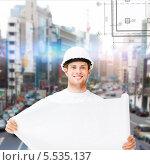 Купить «строитель разворачивает план здания», фото № 5535137, снято 6 июня 2013 г. (c) Syda Productions / Фотобанк Лори