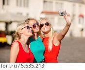 Купить «три девушки фотографируются на камеру смартфона на улице города», фото № 5535213, снято 8 сентября 2013 г. (c) Syda Productions / Фотобанк Лори