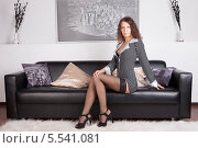 Купить «Девушка в платье и черных чулках сидит на  диване», фото № 5541081, снято 12 июня 2013 г. (c) Литвяк Игорь / Фотобанк Лори