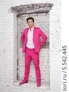 Купить «Молодой человек в розовом костюме и обуви стоит в проеме белой кирпичной стены», фото № 5542445, снято 26 ноября 2012 г. (c) Losevsky Pavel / Фотобанк Лори