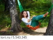 Купить «Молодая женщина с мечтательным выражением лица лежит в гамаке, натянутом между двумя толстыми березами», фото № 5543345, снято 7 августа 2012 г. (c) Losevsky Pavel / Фотобанк Лори
