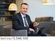 Купить «Бизнесмен в костюме и галстуке сидит на стуле с ноутбуком и телефоном», фото № 5544169, снято 14 февраля 2013 г. (c) Losevsky Pavel / Фотобанк Лори