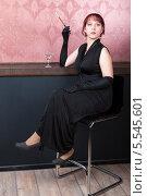 Купить «Женщина в черном платье сидит на барном стуле, пьет коктейль и курит сигарету через мундштук», фото № 5545601, снято 6 декабря 2013 г. (c) Сергей Дубров / Фотобанк Лори