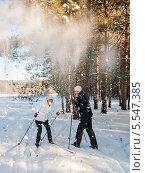 Снег падает на женщин-лыжниц с веток большой сосны. Стоковое фото, фотограф Игорь Низов / Фотобанк Лори