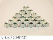 Гайки оцинкованынные сложенные в пирамиду на белом фоне. Стоковое фото, фотограф евгений прысев / Фотобанк Лори