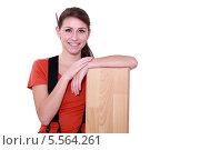улыбающаяся женщина-рабочий облокотилась на планки ламината. Стоковое фото, фотограф Phovoir Images / Фотобанк Лори
