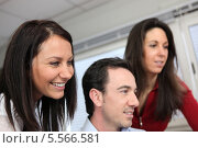 Купить «улыбающиеся коллеги за работой», фото № 5566581, снято 12 февраля 2010 г. (c) Phovoir Images / Фотобанк Лори