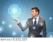 Купить «бизнесмен держит в своей ладони виртуальный контакт», фото № 5572337, снято 3 октября 2013 г. (c) Syda Productions / Фотобанк Лори